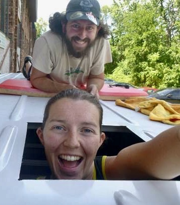 Selfie photo of cheerful white woman and white man on the top of a van